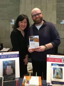 Grace Jin-Sun Kim at the APC Annual Conference with Eerdmans representative, displaying her book Embracing the Other